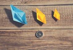 Бумага шлюпки и компаса на деревянной предпосылке стоковая фотография