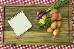 Бумага для рецепта на деревянной доске с листьями картошек, лука и пастернака Стоковое Фото