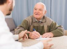 Бумаги подписания человека дома Стоковая Фотография RF