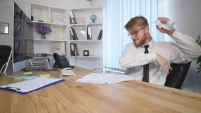 Бумаги сердитого бизнесмена срывая в офисе акции видеоматериалы