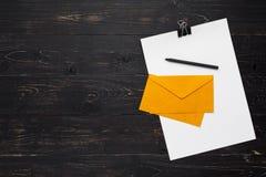 Бумаги с ручкой и конверты на деревянной предпосылке Стоковая Фотография