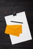 Бумаги с ручкой и конверты на деревянной предпосылке Стоковые Фото