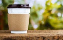 Бумажная кофейная чашка или устранимая чашка на деревянном столе на natura Стоковые Фото