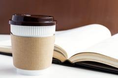 Бумажная кофейная чашка или устранимые чашка и книга на белой таблице b Стоковые Изображения