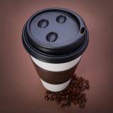 Бумажная кофейная чашка с кофейными зернами на коричневой предпосылке. Вынос Стоковое Фото