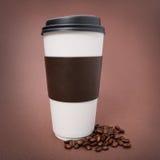 Бумажная кофейная чашка с кофейными зернами на коричневой предпосылке. Вынос Стоковое Изображение