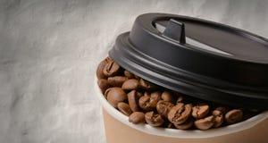 Бумажная кофейная чашка с предпосылкой кофейных зерен Стоковое Изображение