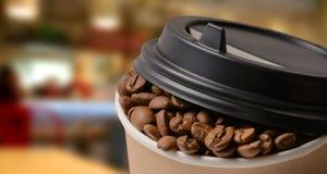 Бумажная кофейная чашка с предпосылкой кофейных зерен Стоковые Фото