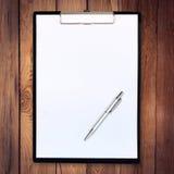 Бумажная доска сзажимом для бумаги на деревянной предпосылке с ручкой Стоковое фото RF