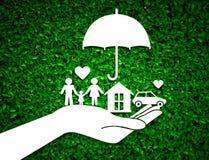 Бумажная рука агента продавца держа предохранение от семьи на зеленом цвете стоковое изображение