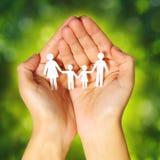 Бумажная семья в руках над зеленой солнечной предпосылкой. Семья Стоковые Фотографии RF