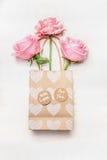 Бумажная хозяйственная сумка с розами и сердце на белой деревянной предпосылке, взгляд сверху Поздравительная открытка дня или дн Стоковое Фото