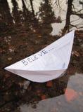 Бумажная шлюпка на воде. Принципиальная схема верит в сновидении Стоковое фото RF