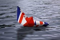Бумажная шлюпка сделанная как великобританский флаг тонуть в воду - показ Англию концепции покидая Европейский союз и экономику и стоковые изображения