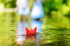Бумажная шлюпка плавая на реку Стоковые Фото