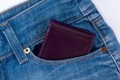 Бумажник лежит в бортовом карманн голубых джинсов стоковая фотография
