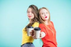 2 бумажного стаканчика кофе на переднем плане, в фокусе Маленькие девочки держа руки Стоковые Изображения RF