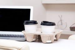 2 бумажного стаканчика стоить о компьтер-книжке на таблице Стоковое фото RF