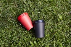 2 бумажного стаканчика с кофе, который нужно принять прочь, красная и черная чашка на завтраке зеленой травы внешнем Стоковые Фото