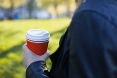 Бумажное красное стекло с белыми крышкой и кофе в руках девушки Стоковые Фото