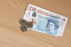 Бумажные деньги английского фунта стерлинговые с монетками стоковые изображения rf