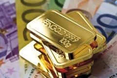 Бумажные деньги золота в слитках и евро Стоковые Изображения