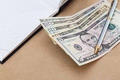 Бумажные деньги, дневник и ручка взгляда различные стоковые фото