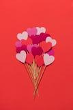 Бумажные сердца на деревянных ручках на красной предпосылке Стоковые Изображения