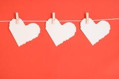 Бумажные сердца на красной предпосылке Стоковые Изображения