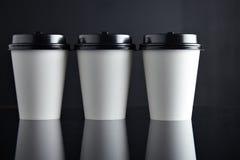 Бумажные стаканчики белого роскошного взятия отсутствующие установили черноту отраженный Стоковое Изображение