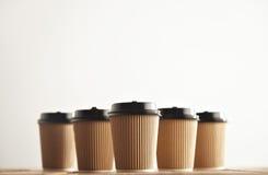 Бумажные стаканчики взятия картона Брайна отсутствующие при черные установленные крышки Стоковая Фотография RF