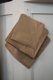 Бумажные сумки вися на деревянном кухонном шкафе Стоковая Фотография