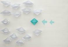 бумажные шлюпки и уникально различная шлюпка сделали плавать напротив пути другого одни Стоковое Изображение RF