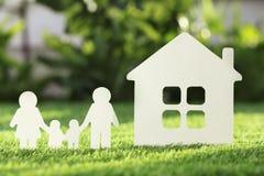 Бумажный вырез семьи и дома на свежей траве стоковое фото rf