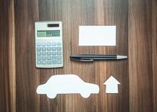 Бумажный дом с автомобилем и калькулятором на древесине Стоковое Фото