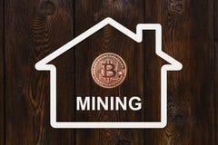 Бумажный дом с bitcoin внутри и МИНИРОВАНИЕМ текста Абстрактная принципиальная схема Стоковое Фото