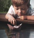 Бумажный корабль в детях вручает стоковая фотография