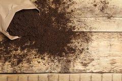 Бумажный мешок и почва на деревянном столе, космосе для текста Садовничая сезон стоковая фотография