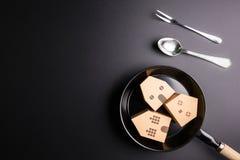Бумажный дом в сковороде изолированной на черном backgroun Стоковые Изображения RF