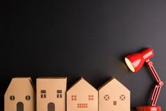 Бумажный дом и красная лампа на черной предпосылке с экземпляром Стоковое Фото