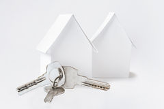 Бумажный дом 2 и ключи на белом экземпляре размечают предпосылку Стоковое фото RF
