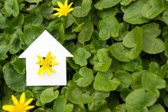 Бумажный дом против зеленой предпосылки имущество принципиальной схемы реальное Стоковые Изображения