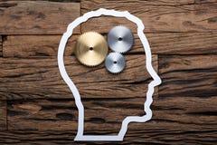 Бумажный план головы ` s бизнесмена с металлическими шестернями на таблице стоковое фото