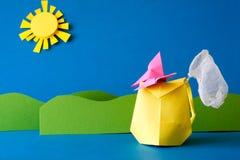Бумажный рюкзак с сетью бабочки на поле травы на голубой предпосылке Приключение лета Располагающся лагерем и концепция пешего ту Стоковая Фотография