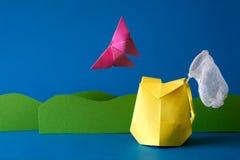 Бумажный рюкзак с сетью бабочки на поле травы на голубой предпосылке Приключение лета Располагающся лагерем и концепция пешего ту Стоковое Изображение RF