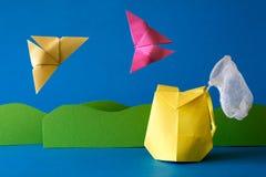 Бумажный рюкзак с сетью бабочки на поле травы на голубой предпосылке Приключение лета Располагающся лагерем и концепция пешего ту Стоковое фото RF