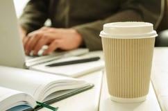 Бумажный стаканчик кофе на работ-таблице с веществом офиса, блокнотом, компьтер-книжкой, ручкой, кофейной чашкой и деятеля на пре стоковое фото