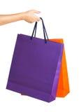 2 бумажных хозяйственной сумки в руке женщины с отражением на белизне Стоковые Изображения RF