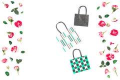 3 бумажных хозяйственной сумки и розовой рамка цветков на белой предпосылке Взгляд сверху Стоковые Фотографии RF
