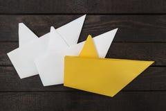 3 бумажных шлюпки на темной деревянной предпосылке Стоковая Фотография